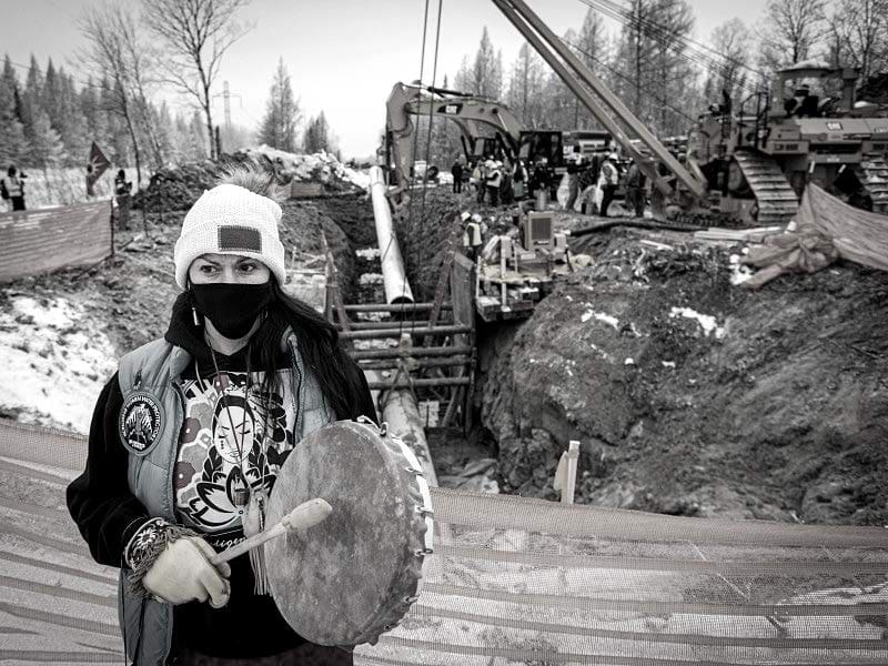 Earthjustice. Gio Cerise, a member of the White Earth Nation, plays a drum and prays in front of Line 3 pipeline construction on Highway 169 south of Hill City, Minn.